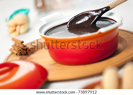 A ceramic pot of neapolitan sanguinaccio chocolate sauce with a wooden spoon dipped into and cinnamon sticks on the plate - stock photo