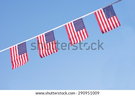 A chain / garland/ bunting of USA flags hanging proudly for July 4 Independence Day - stock photo
