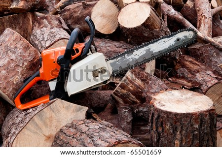 A chain saw sitting on a pile of logs - stock photo