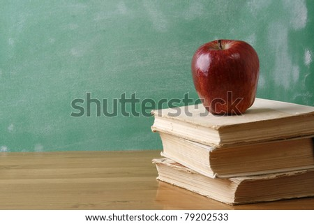 A chalkboard with an apple and a pile of books on a wooden table - stock photo
