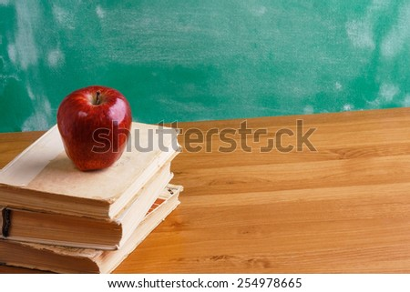 A chalkboard with an apple over books on a wooden desk - stock photo