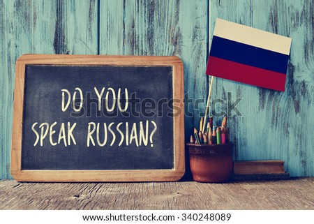 a chalkboard with the question do you speak russian? written in it, a pot with pencils, some books and the flag of Russia, on a wooden desk - stock photo