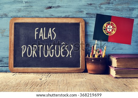 a chalkboard with the question question falas portuges? do you speak Portuguese? written in Portugese, a pot with pencils, some books and the flag of Portugal, on a wooden desk - stock photo