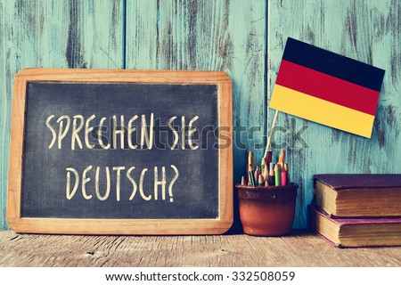 a chalkboard with the question sprechen sie deutsch? do you speak german? written in german, a pot with pencils, some books and the flag of Germany, on a wooden desk - stock photo