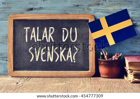 a chalkboard with the question talar du svenska?, do you speak Swedish? written in Swedish, a pot with pencils, some books and the flag of Sweden, on a wooden desk - stock photo