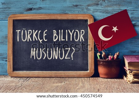 a chalkboard with the question turkce biliyor musunuz?, do you speak Turkish? written in Turkish, a pot with pencils, some books and the flag of Turkey, on a wooden desk - stock photo