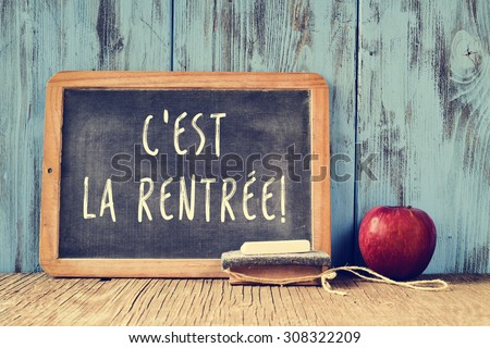 a chalkboard with the text cest la rentree, back to school in french written in it, a piece of chalk, an eraser and a red apple on a rustic wooden table, cross processed - stock photo