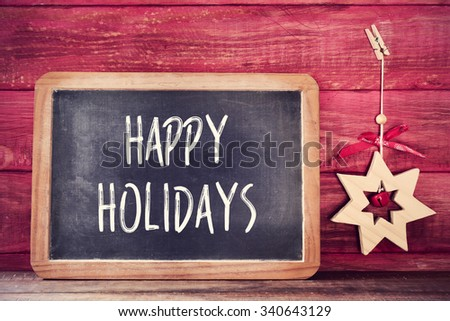 a chalkboard with the text happy holidays written in it and a wooden christmas star on a red rustic wooden surface - stock photo