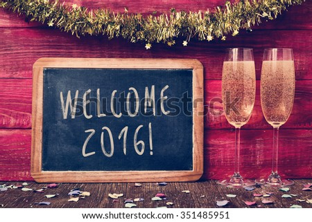 a chalkboard with the text welcome 2016 written in it, some confetti and a pair of glasses with champagne on a red rustic wooden background ornamented with tinsel - stock photo