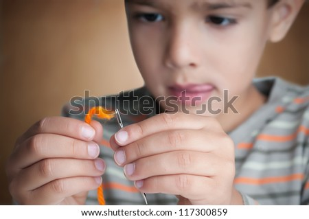A challenge concept by a child trying to put a wool in to a needle hall - stock photo