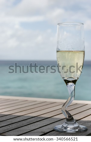 A champagne glass by the ocean, time for celebration taken at Maldives
