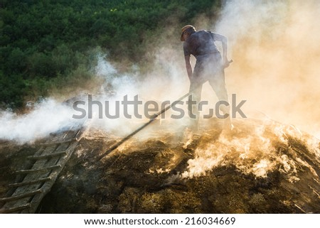 A charcoal maker at work on a pile of slow burning wood with very little oxygen.