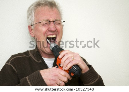 A charicature use of a drill. This man wants to play self-dentist... Not very wise. - stock photo