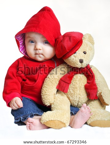 A charming baby girl holding a toy bear