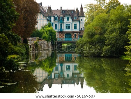 A charming castle on a small river in France.  The castle is built across the river and casts a reflection in the water.  Lots of greenery on both sides of the river. - stock photo