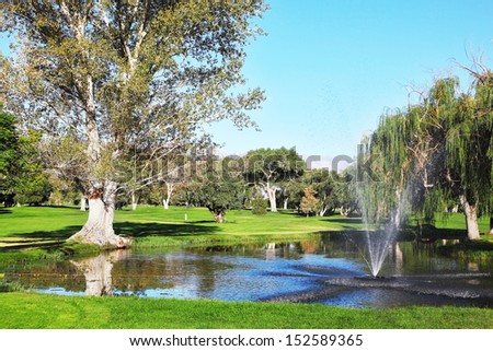 A charming decorative fountain at the golf course, against the background of distant mountains