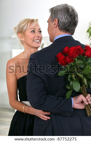 A charming gentleman hiding roses behind his back - stock photo