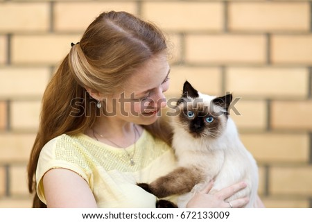 A charming long-haired girl is holding a fluffy blue-eyed cat. It looks like a sacred Burma (Burmese cat), Thai cat, Siberian or Neva Masquerade. The girl smiles sincerely.