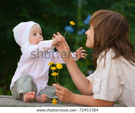 A charming one-year child gives a flower to his mother - stock photo