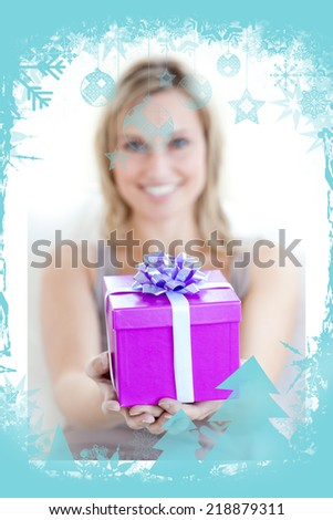 A charming woman is holding a present against christmas frame - stock photo