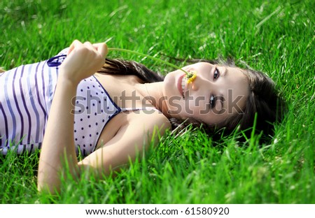 a charming young woman lying on a summer meadow