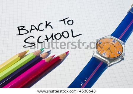 """A checked paper with the words """"back to school"""" in it. There are some color pencils and a kid clock in the borders. - stock photo"""