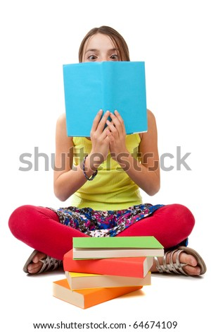 A cheeky girl sits with crossed eyes and legs peeking over the top of her blue book.  A stack of multi-coloured books is in front of her.