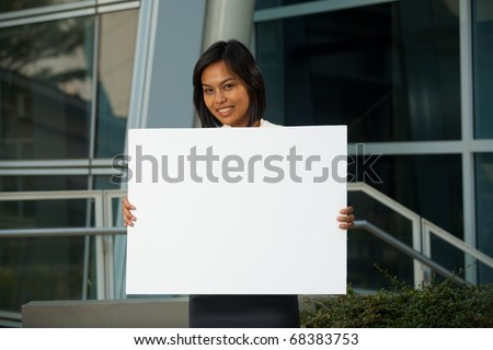 A cheerful and cute Asian corporate professional holds an empty white placard in front of office building. Custom text insert. Female Asian Thai model of Chinese descent looking at camera