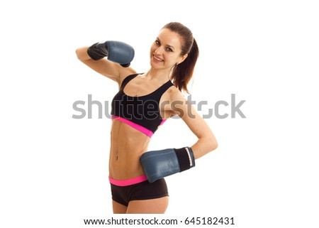 a cheerful athletic girl stands in boxing gloves and short shorts in front of the camera and smiling