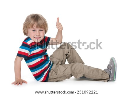 A cheerful blond boy sits on the floor and holds his thumb up against the white background - stock photo