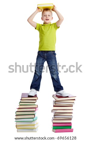 A cheerful boy with a book standing on two heaps of books - stock photo