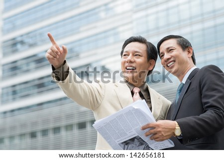 A cheerful businessman showing something to his colleagues outside - stock photo