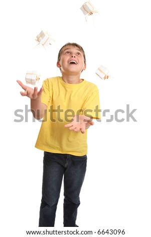 A cheerful child dressed in plain t-shirt and denim jeans juggling small giftboxed presents - stock photo