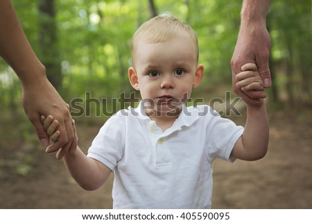 A Cheerful Child hold the Parent Hand in the Summer Park - stock photo