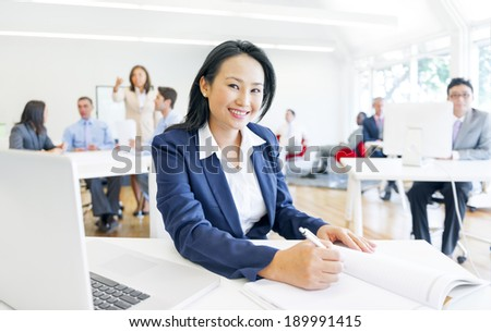 A Cheerful Corporate woman Doing her Paperworks - stock photo