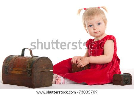 A cheerful girl dressed in a red dress is sitting among the wooden chests; isolated on the white background - stock photo