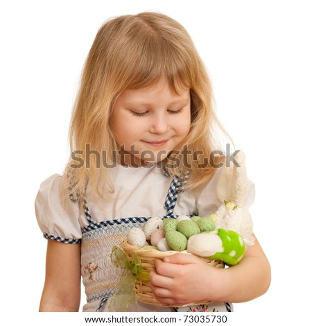 A cheerful girl is holding an easter basket full of toy eggs; isolated on the white background - stock photo