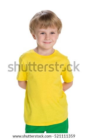 A cheerful little boy in a yellow shirt stands against the white background