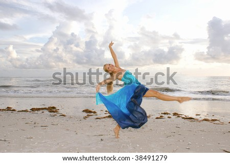 A cheerful pretty adult female ballerina is dancing on the beach with her arms up and her leg extended looking at you the viewer with a big smile. - stock photo