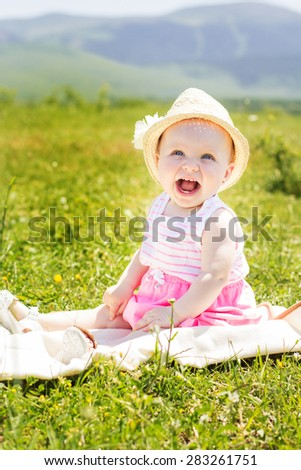 A cheerful smiling baby girl is wearing hat and sitting on the grass - stock photo