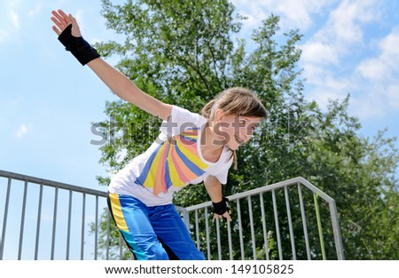 A cheerful teenage girl enjoying during skating practice in the park. - stock photo