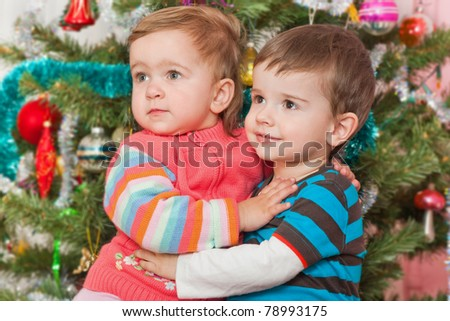 A cheerful toddler is hugging a little girl at the decorated New Year tree