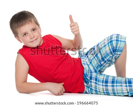 A cheerful young boy sits on the floor and holds his thumb up against the white background - stock photo