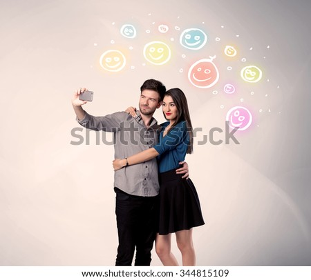 A cheerful young couple taking selfie photo with mobile phone and colorful happy smiley faces illustration above them concept - stock photo