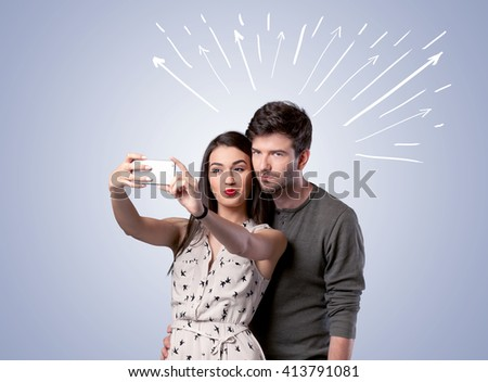 A cheerful young couple taking selfie photo with mobile phone and white lines and arrows pointing to the sky above them concept - stock photo
