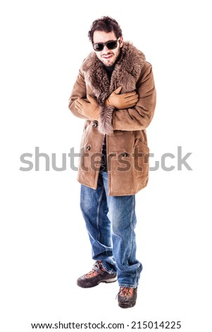 a cheerful young man wearing an expensive sheepskin furry coat isolated over a white background and shivering for the cold - stock photo