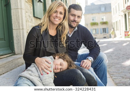 A Cheerful young parents with kid in an urban scene  - stock photo