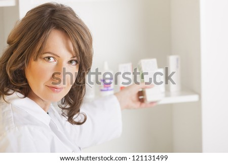 A cheerful young woman pharmacist with a bottle of drugs standing in pharmacy drugstore - stock photo