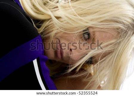 A cheerleader has her head on her knee and a serious face - stock photo