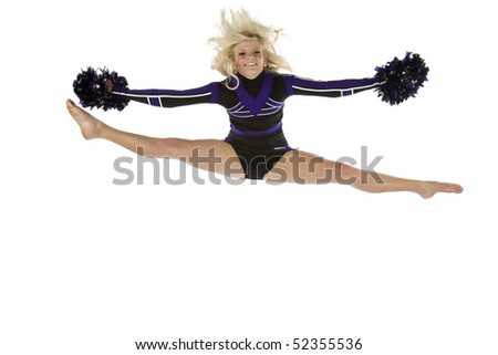 A cheerleader has jumped into the air in the splits position with a smile on her face. - stock photo